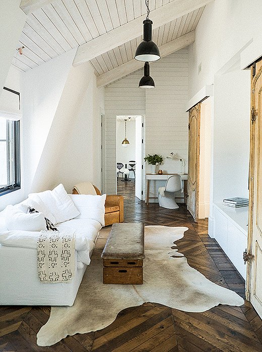 All the classic Danish minimalist elements are addressed in this room -natural wood floors &doors and white painted walls;the cognac leather armchair,vintage trunk and hide rug add a touch of warm minimalism.  Photo by  Josh Franer, One Kings Lane