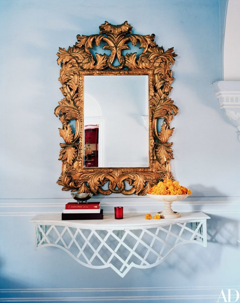 18th century ornately carved mirror that fits right in with the console's spare trellis design