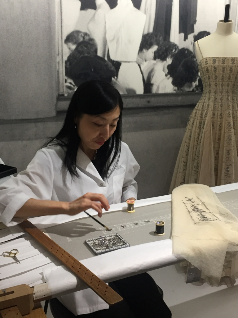 This extraordinary seamstress is fully immersed in her zen task of applying by hand individual beads and sequins to the couture gown behind her - it will take approximately 500 hours to complete