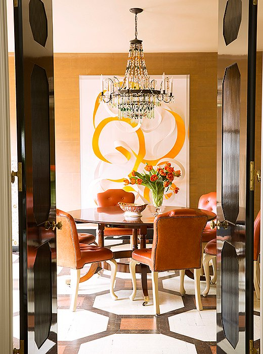 This is one of my favorite dining rooms because its pops of orange leather dining chairs and stenciled floor make it so dynamic...there's all manner of design inspo here.. . photography One Kings Lane
