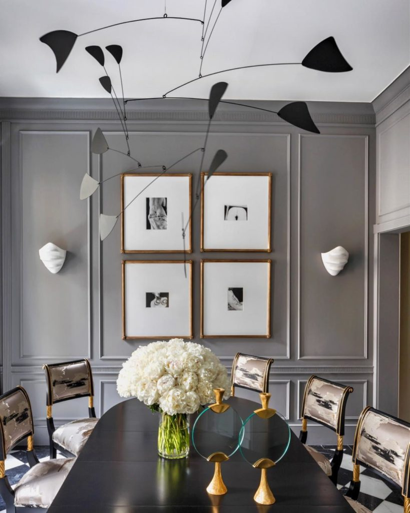 The contemporary lighting reminiscent of an Alexander Calder mobile adds a distinctly playful edge to the formal dining room...liberal use of gold and bronze finishes warm up the austere gray tones