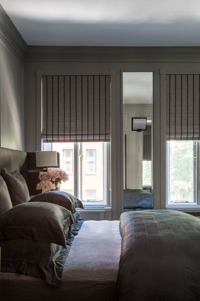 The striped fabric shades, bedding and center mirrored panel -perfect