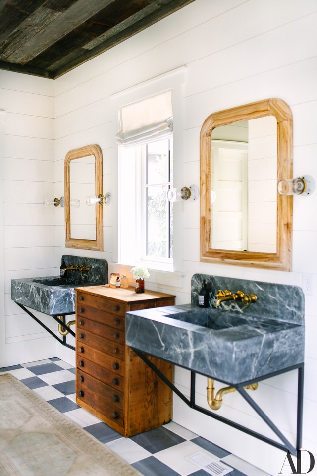 Antique cabinet brings a rustic note to this polished master bathroom. Room design by  Brooklyn Decker - Architectural Digest