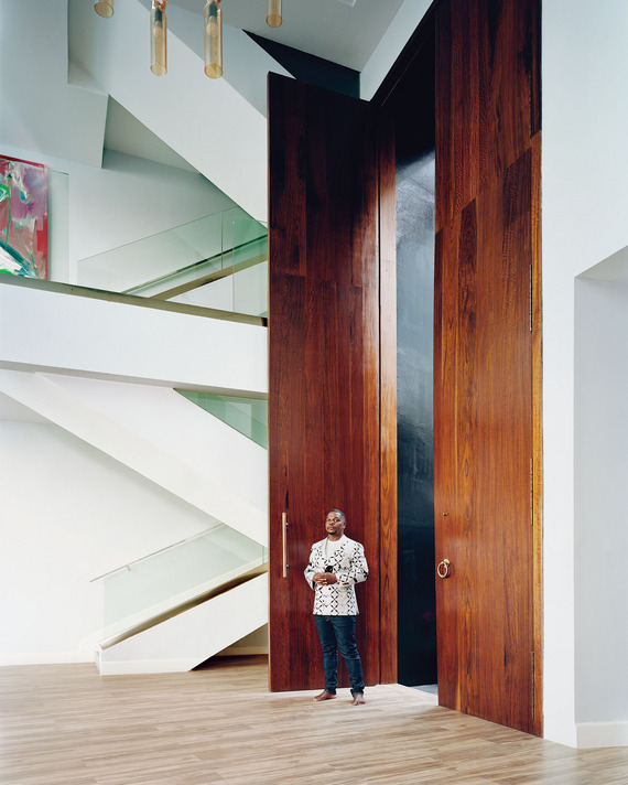 Kehinde standing beside his front doors perfectly captures their immense scale