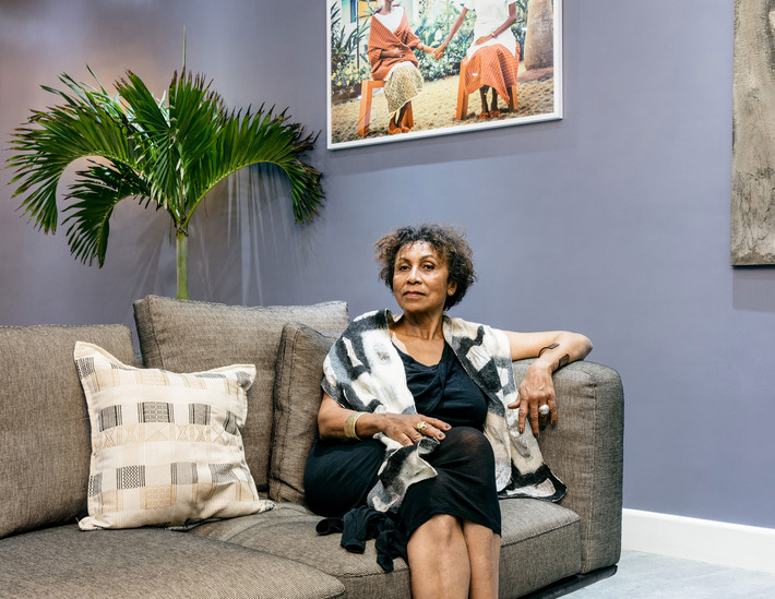 Aissa Dione designer of the Interiors and textiles reclines on a sectional of her design