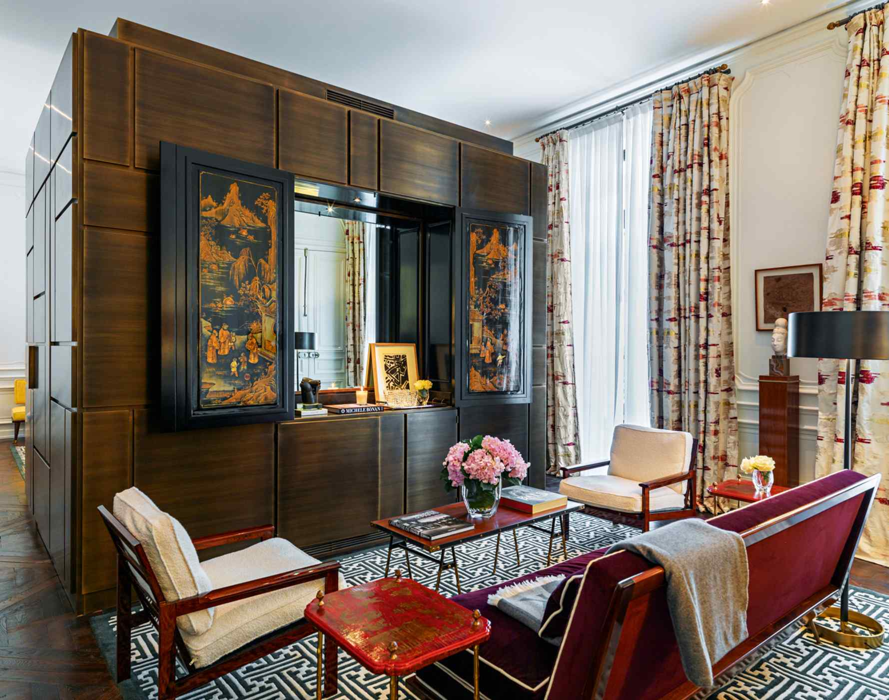 Positioned in the middle of the room of this suite is the ingenious design of a hand-crafted double-sided cabinet carved from oak decapé - antique Chinese panels face the living area while the back transforms into the bed's headboard and a closet