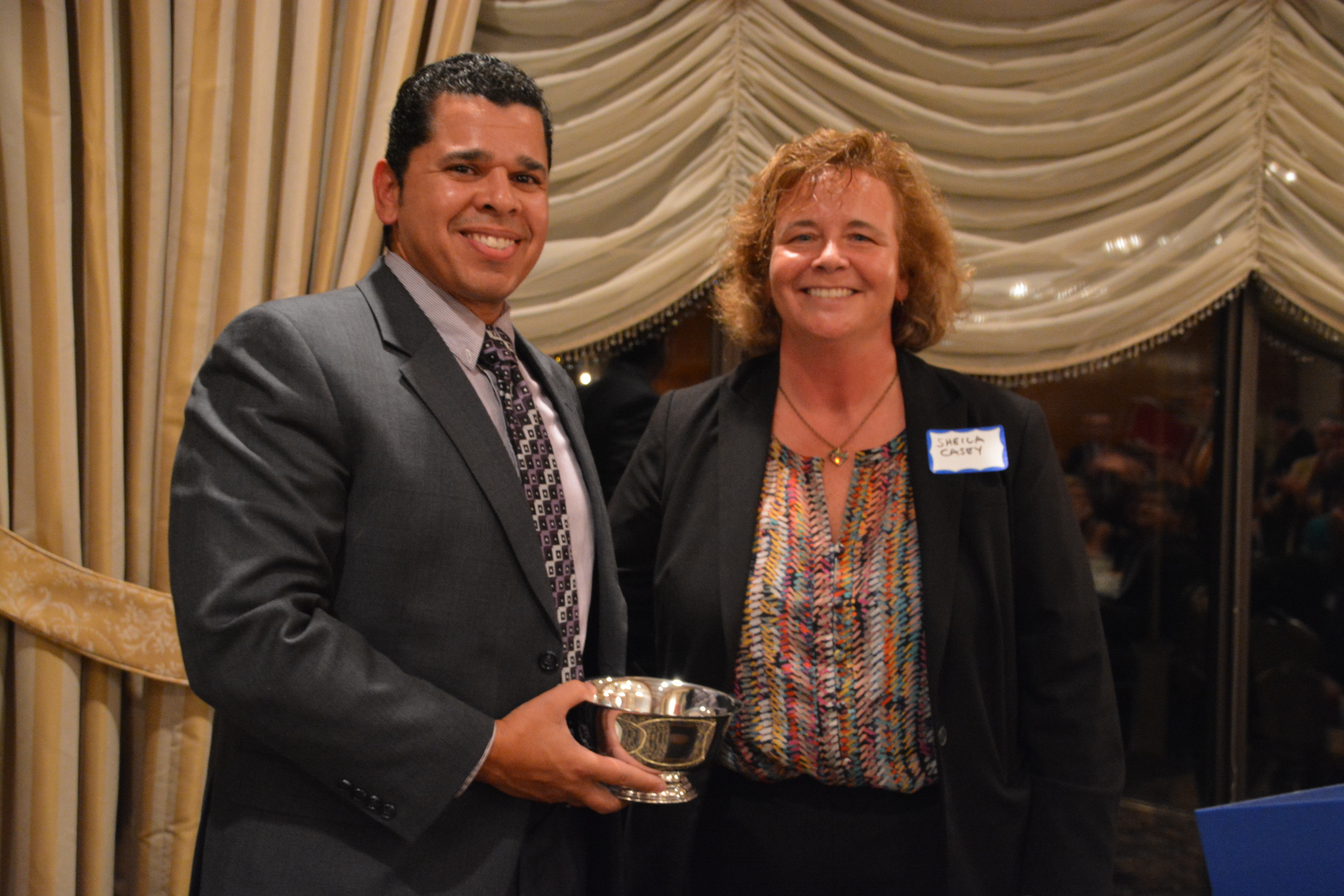 The LBA's Sheila Casey awarded this year's Liberty Bell Award to Juan Bonilla, Deputy Director of Lawrence Community Works