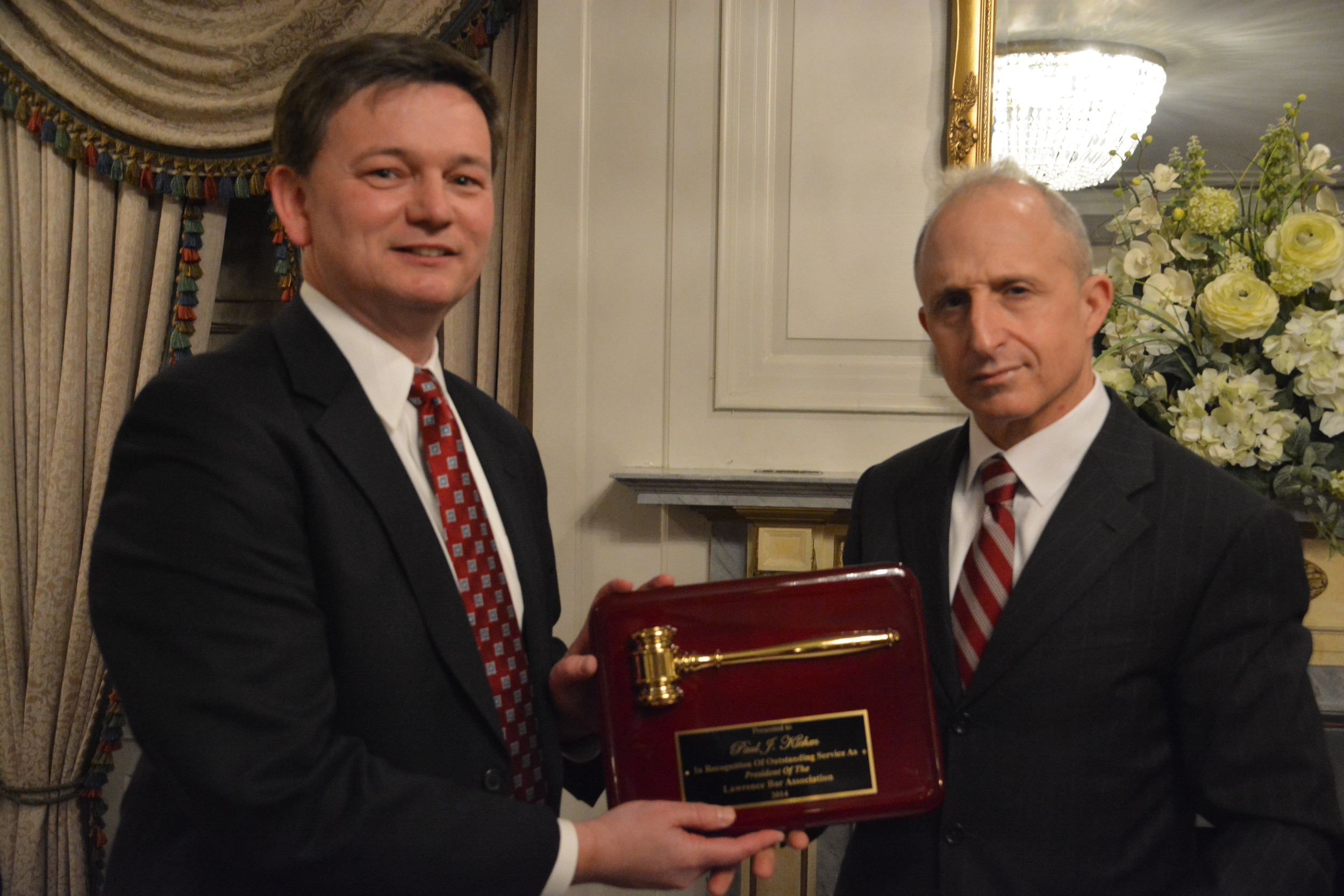 Outgoing President Paul Klehm receives the presidential plaque from the LBA's new president, Mark Machera.