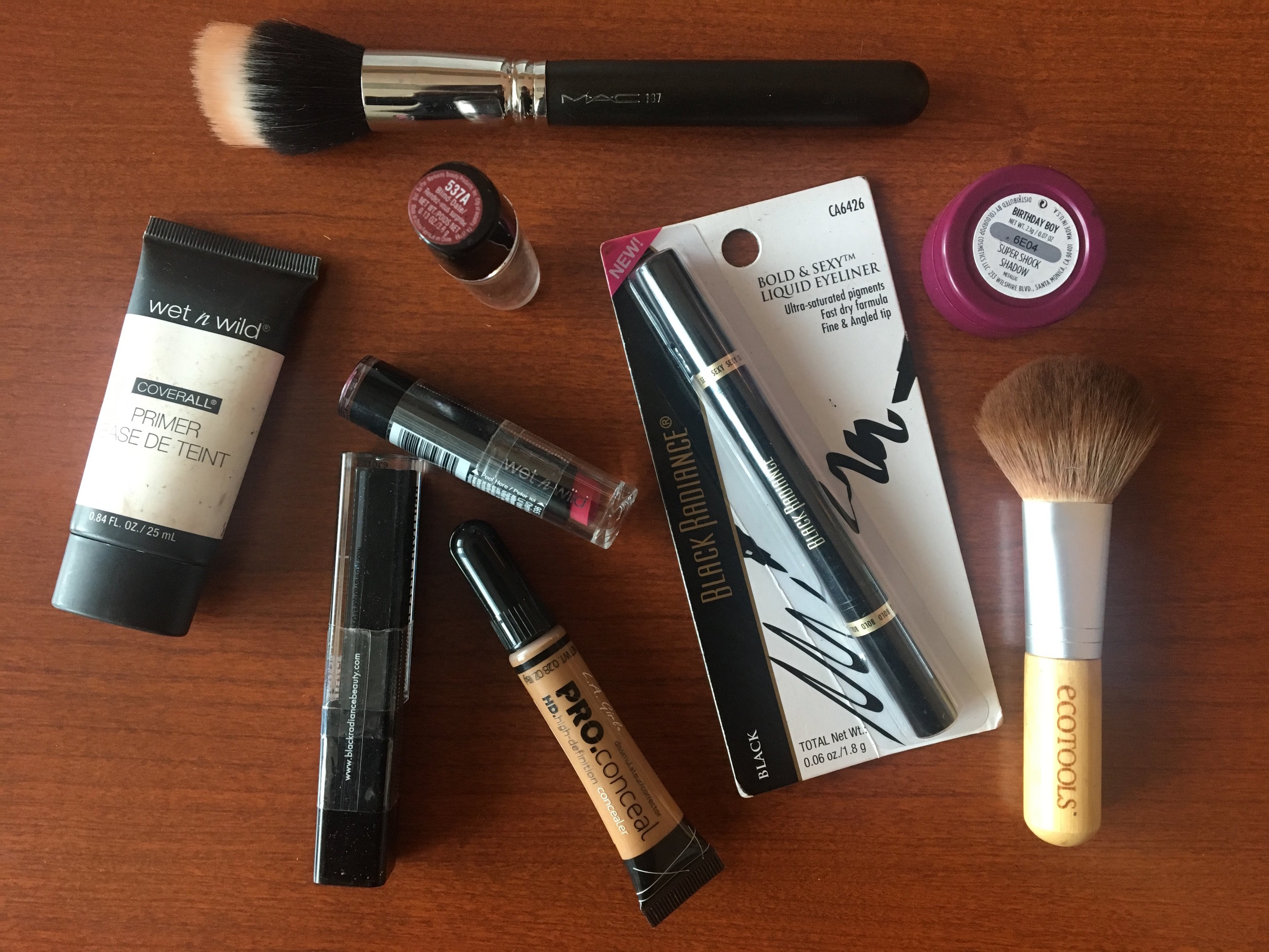 Wet n Wild primer, Black Radiance lipgloss (Black Diamond), Black Radiance liquid eyeliner (Black), Wet n Wild lipstick (Blind Date and Cherry Picking), L.A. Girl PRO Conceal concealer(Fawn), EcoTools blush brush, MAC foundation brush #187, Color Pop eyeshadow (Birthday Boy).
