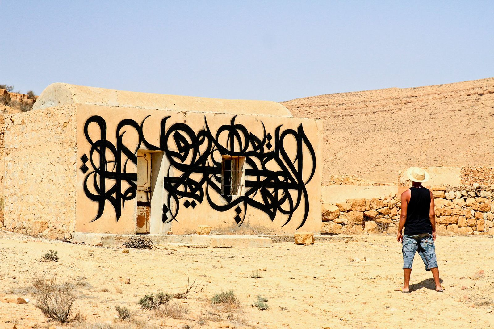 """eL Seed, 'The Original Source', Ksar Hadada, Tunisia, from the """"Lost Walls"""" project, 2013. Photograph by Ouahid Berrehouma."""