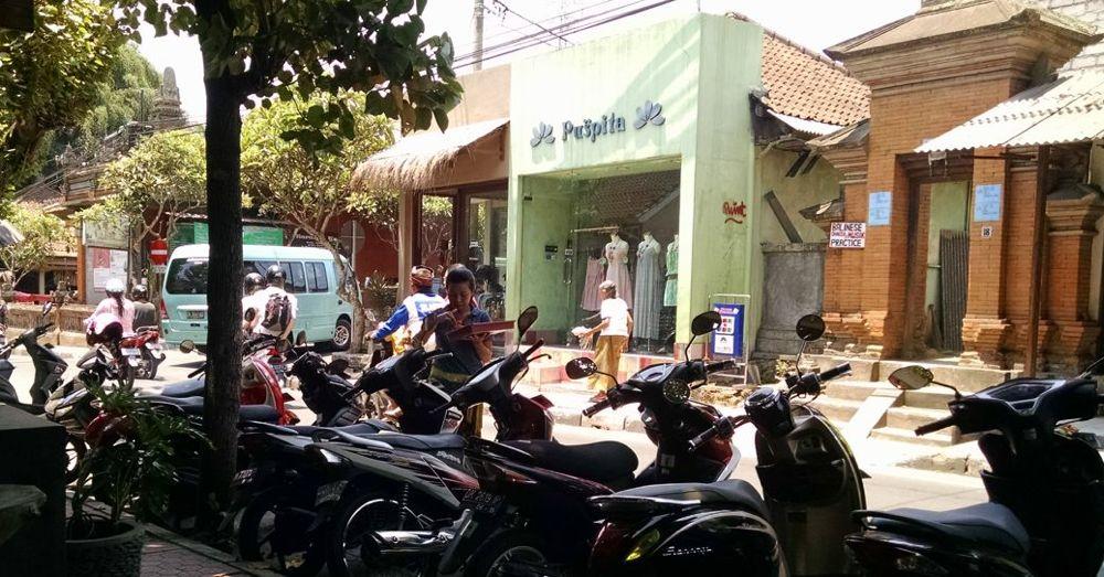 Woman placing a canang sari on a motorbike.