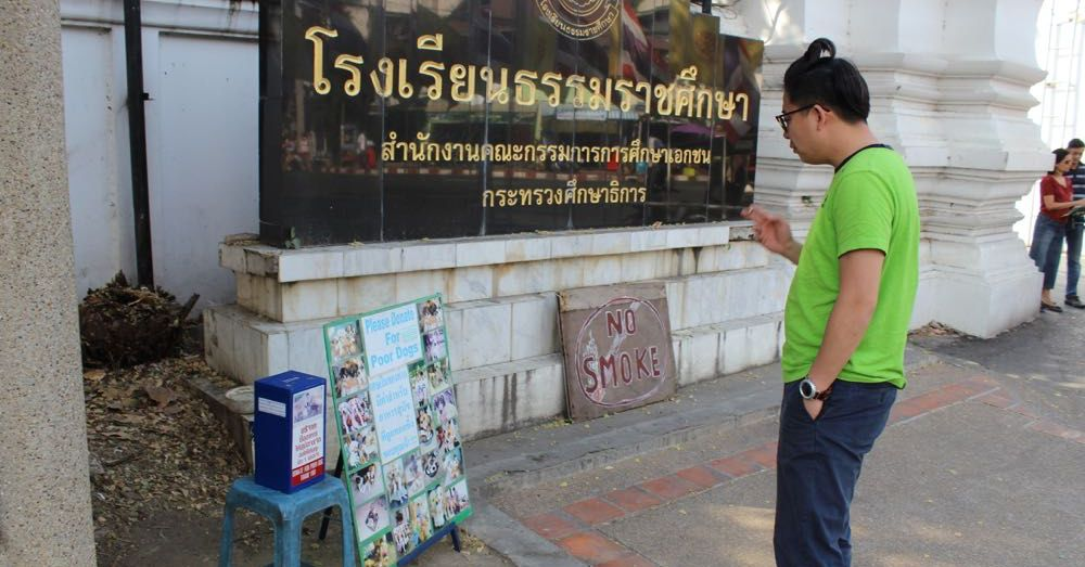 Dude Smoking in Front of a No Smoke Sign