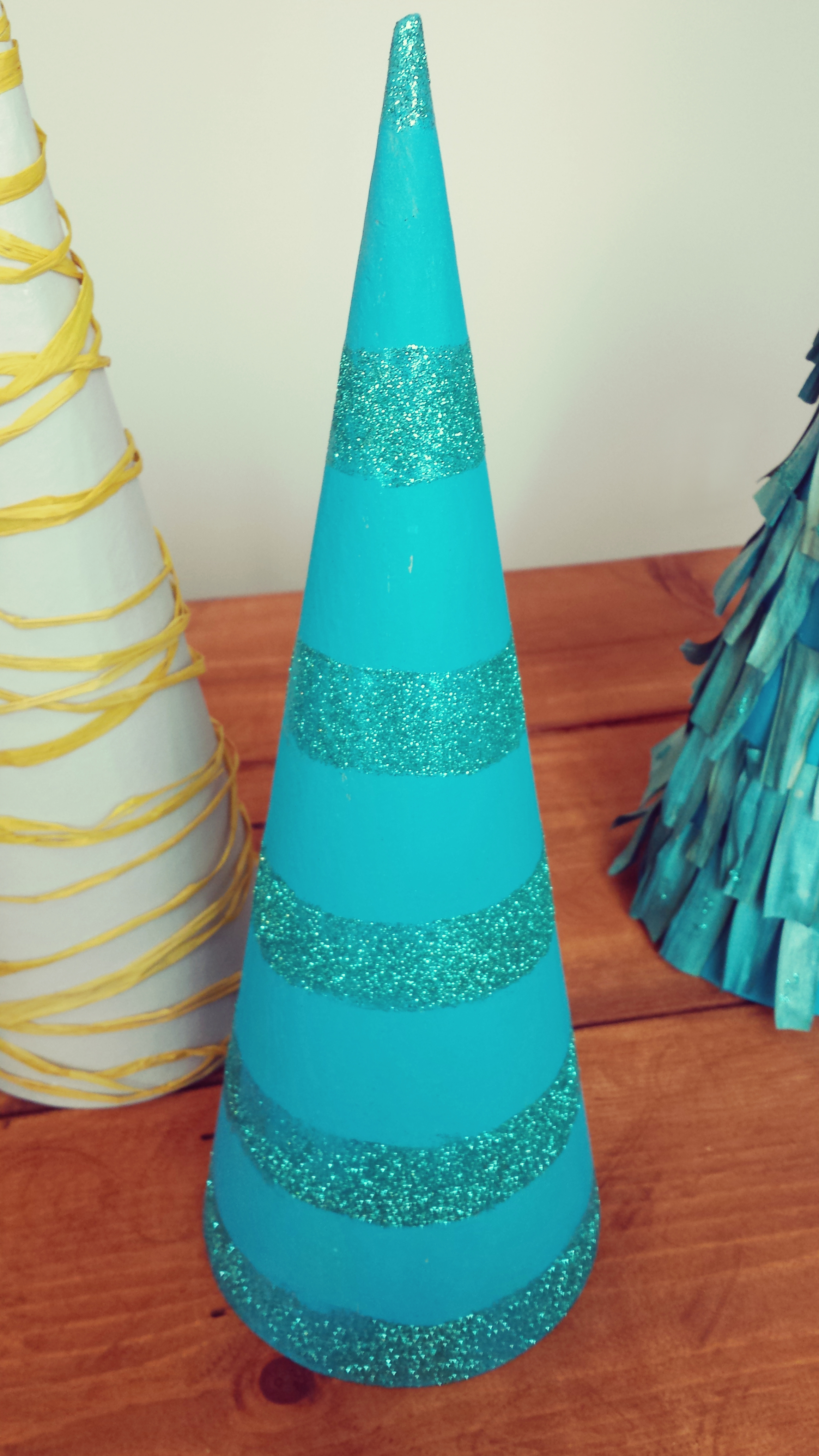For the glitter tree I simply painted it with the acrylic paint with a cheap foam brush and let it dry. You don't need a lot of paint so it will dry fast. Then I use another foam brush and applied glued on the areas I wanted my stripes. I winged this one but if you don't feel comfortable with that simply use a ruler and pencil and mark the circumference in the areas you want it. It doesn't have to be perfect. For the Raffia Tree I took one end of a raffia string and glued it on the bottom then I began to wrap it around and put glue every now and then where needed.