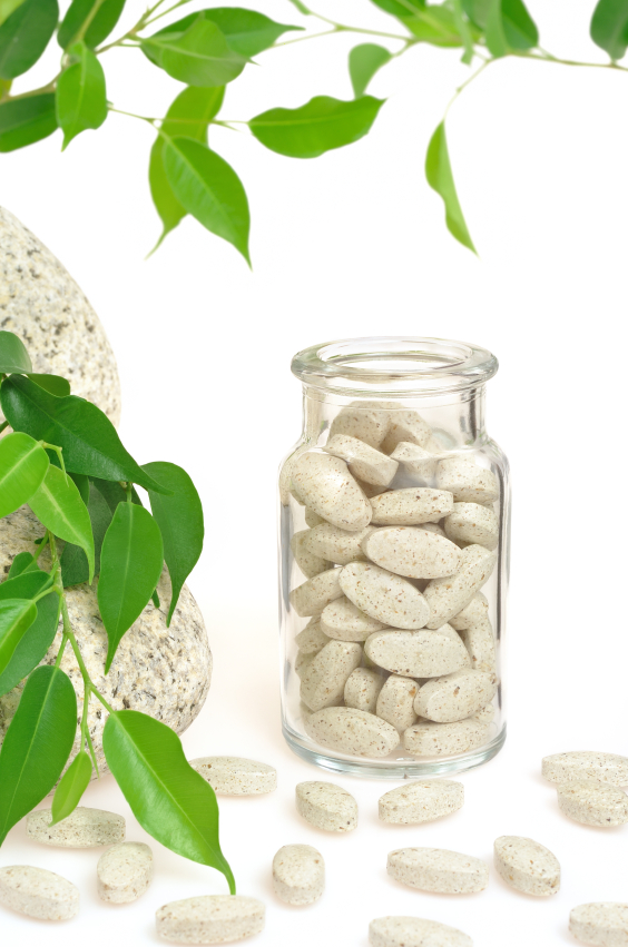 Food supplement in a glass bottle next to a green plant laying on a rock