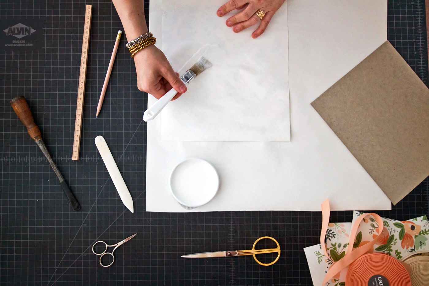 Step 2: Working quickly brush the glue onto the back of your paper. Then transfer your cardboard to the center and press down, working out any air bubbles with your hands or bone folder.