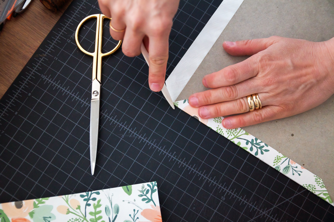 Step 4: Fold the first side over. Then using your bone folder, press the corner paper in towards the next fold so it lays against the cardboard edge. Then fold the second side down. Repeat as you go around.