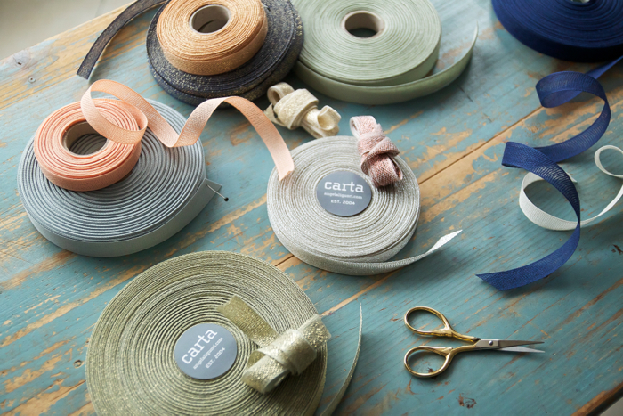 Supplies: With a wedding or shower in mind, we choose a pastel assortment of  Studio Carta  wide loose and tight weave ribbon in natural cotton and wide metallic loose weave. Of course, by using different ribbons and flowers, this garland can be adapted to fit any palette.