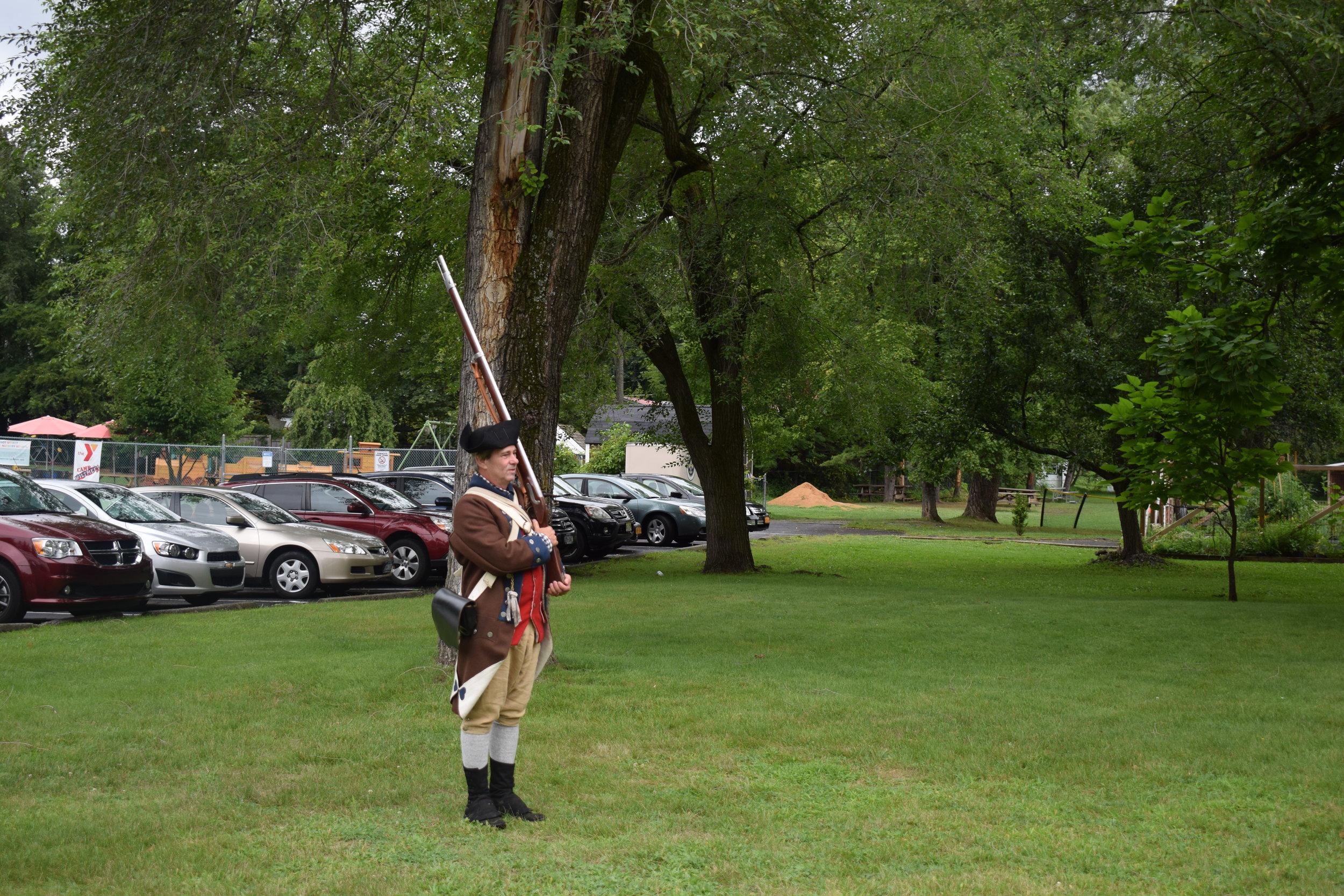Reenactor LeRoy Hogan prepares his musket