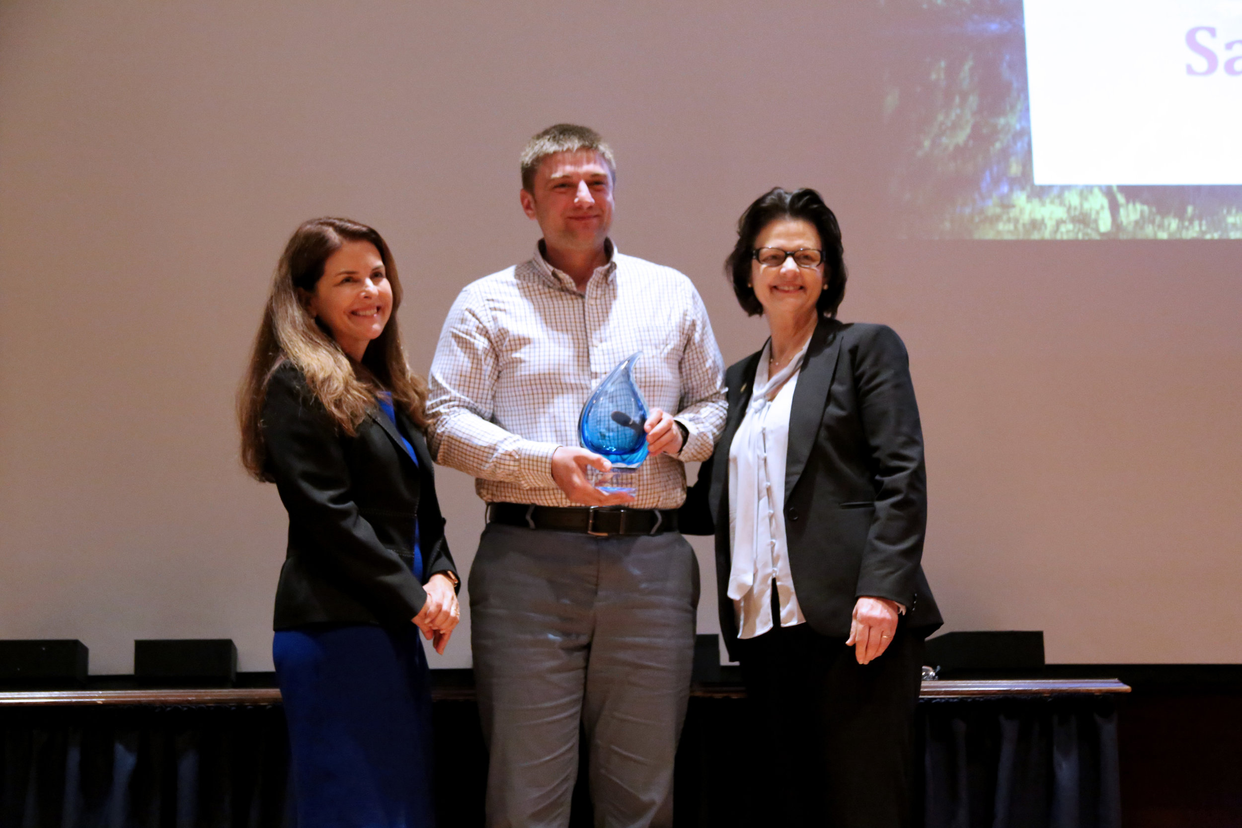 Dr. Bogdan Jackson-Duda with Samuel Jackson, Inc. accepts the Blue Legacy in Manufacturing Award from Water Conservation Advisory Council Chair Karen Guz (L) and Texas Water Development Board Member Kathleen Jackson (R). (Photo courtesy TWDB)