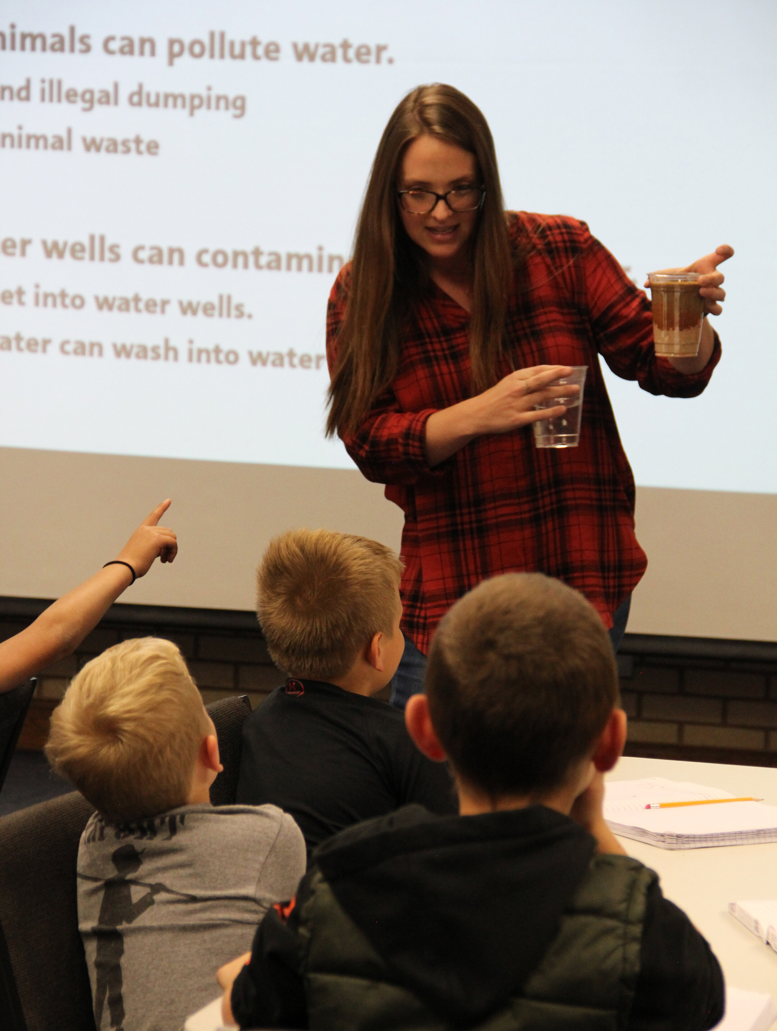 "HPWD Education and Outreach Coordinator Katherine Drury uses a ""mini aquifer"" to demonstrate groundwater contamination to elementary school students from Slaton. The students and their teacher visited the HPWD office during an Oct. 23 field trip to the HPWD office."