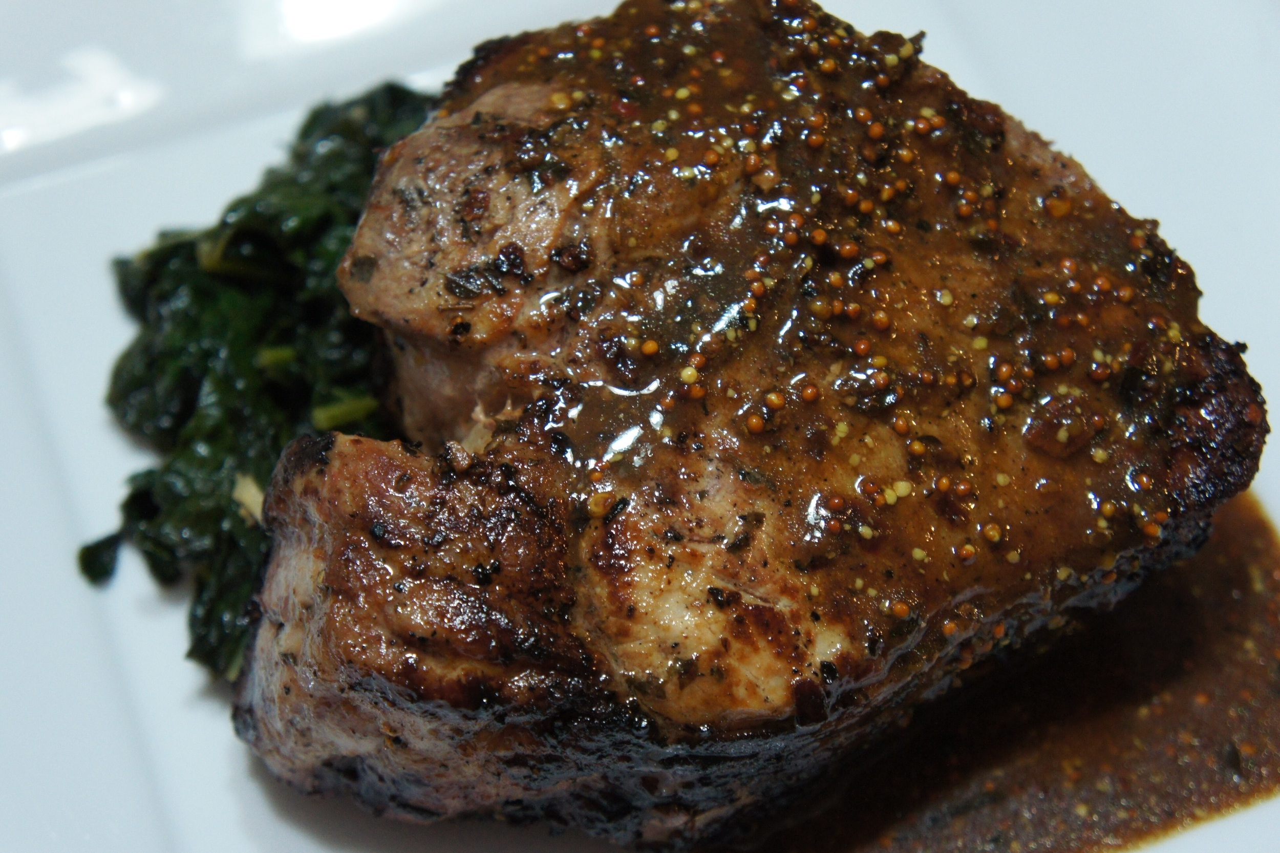 Lemon, thyme and garlic marinated chop, with Fat Tire Ale mustard sauce over sautéed kale.