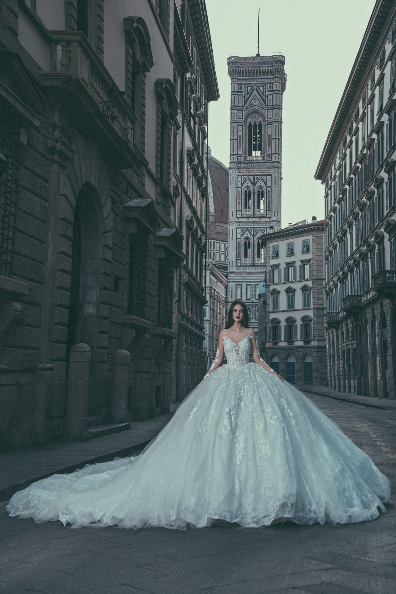 CB Couture #01 - This long sleeve lace mermaid wedding gown features a detachable skirt and is embellished with crystals and pearls. The illusion back leads into an exposed zipper with crystal beading and buttons going up the back. Also features a royal cathedral train.