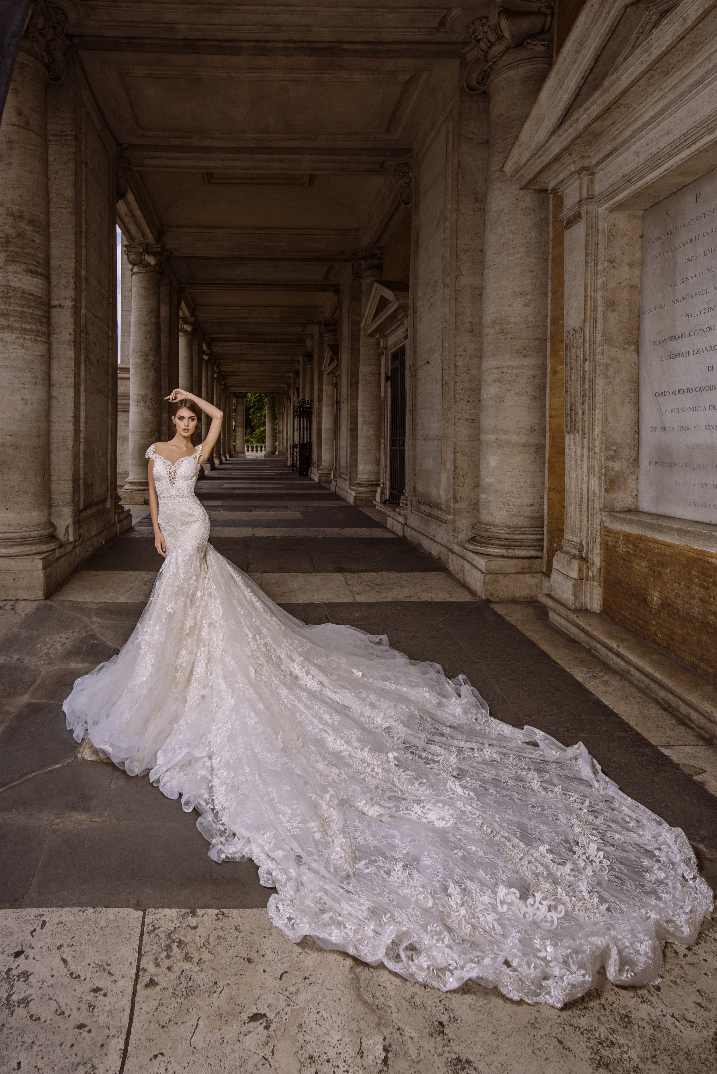 Julia Kontogruni - This long sleeve lace mermaid wedding gown features a detachable skirt and is embellished with crystals and pearls. The illusion back leads into an exposed zipper with crystal beading and buttons going up the back. Also features a royal cathedral train.