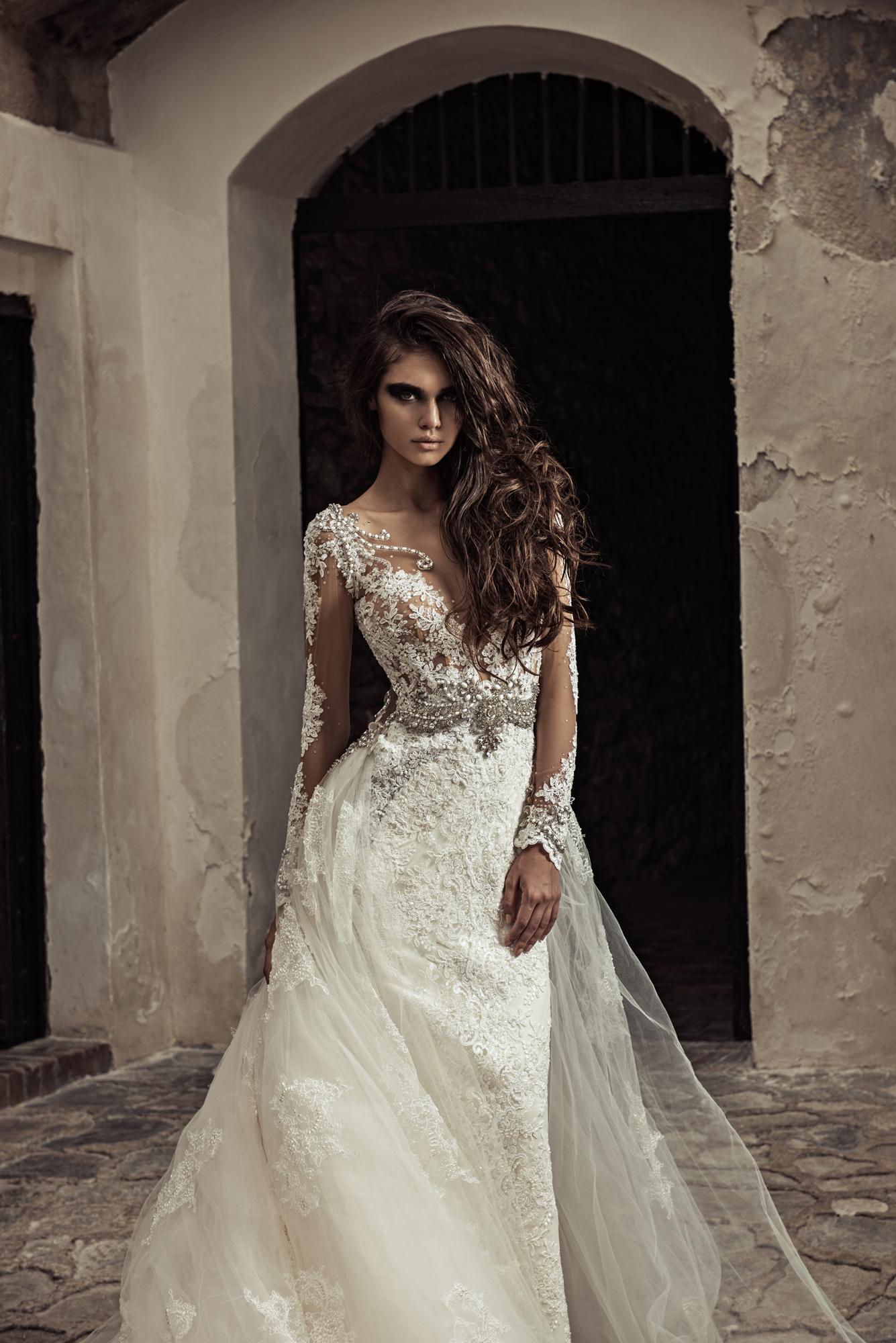 1713 - This long sleeve lace mermaid wedding gown features a detachable skirt and is embellished with crystals and pearls. The illusion back leads into an exposed zipper with crystal beading and buttons going up the back. Also features a royal cathedral train.