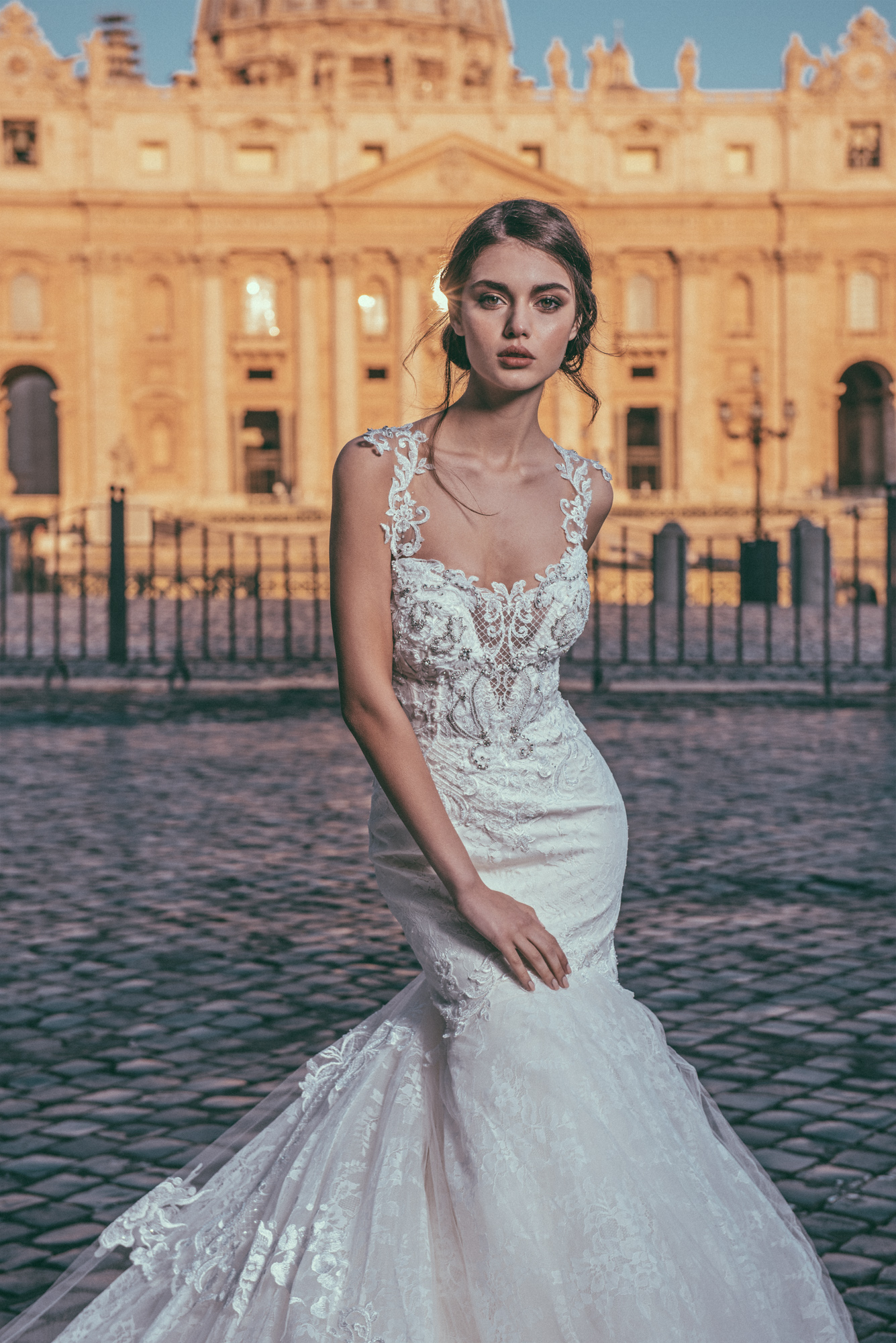 JK Couture #13 - This long sleeve lace mermaid wedding gown features a detachable skirt and is embellished with crystals and pearls. The illusion back leads into an exposed zipper with crystal beading and buttons going up the back. Also features a royal cathedral train.