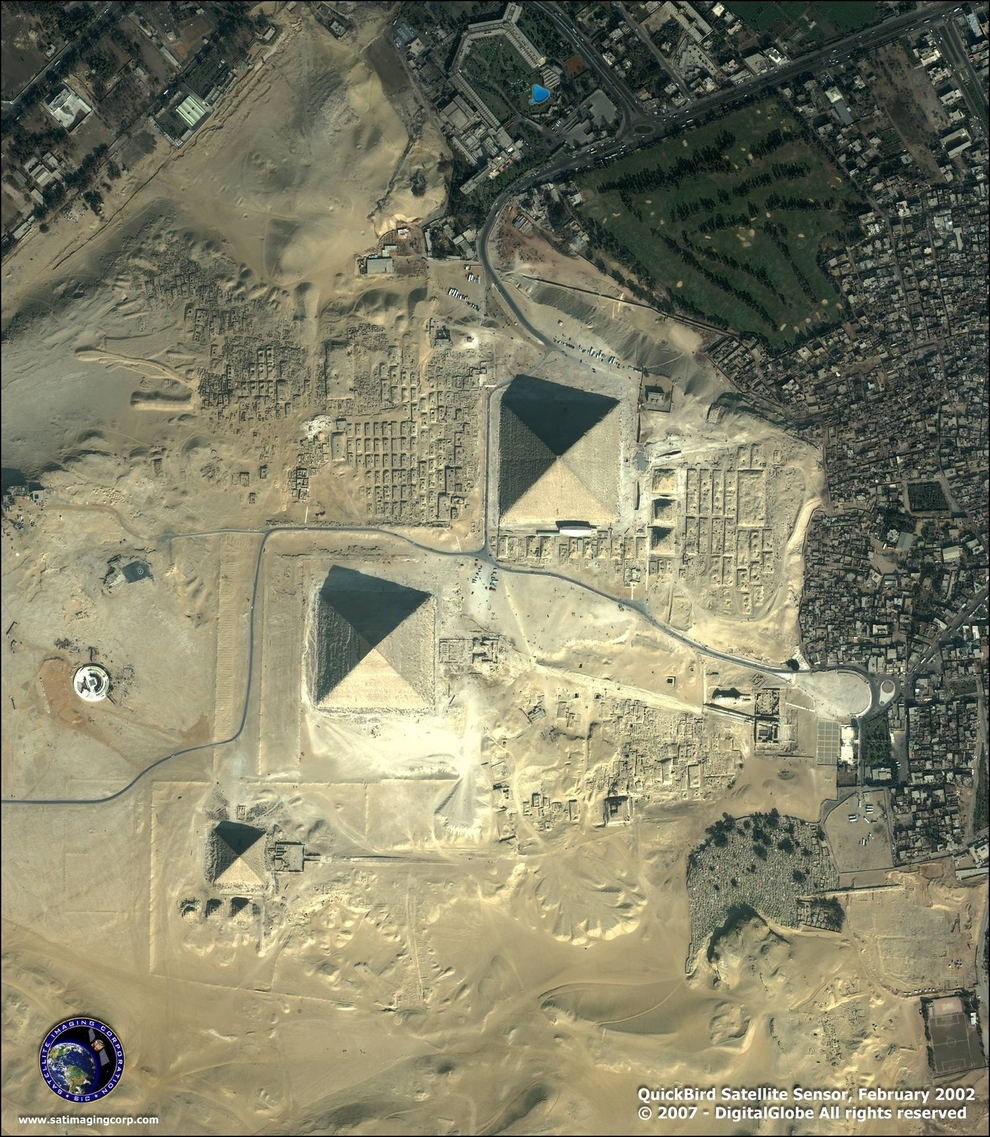 The Pyramids at Giza, Egypt    One thing you never quite get a sense of by looking at people's pictures of the Pyramids is just how close the city of Cairo presses up around them. If you look at the center left of the picture—right beneath the meandering road that leads into the Pyramids, you can see the Great Sphinx, too ( via )