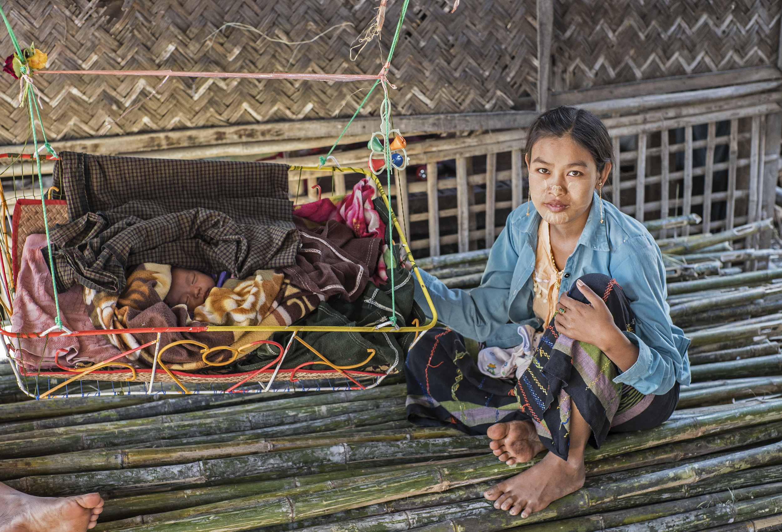 Young woman takes care of her much younger family member in Myanmar's dry zone.