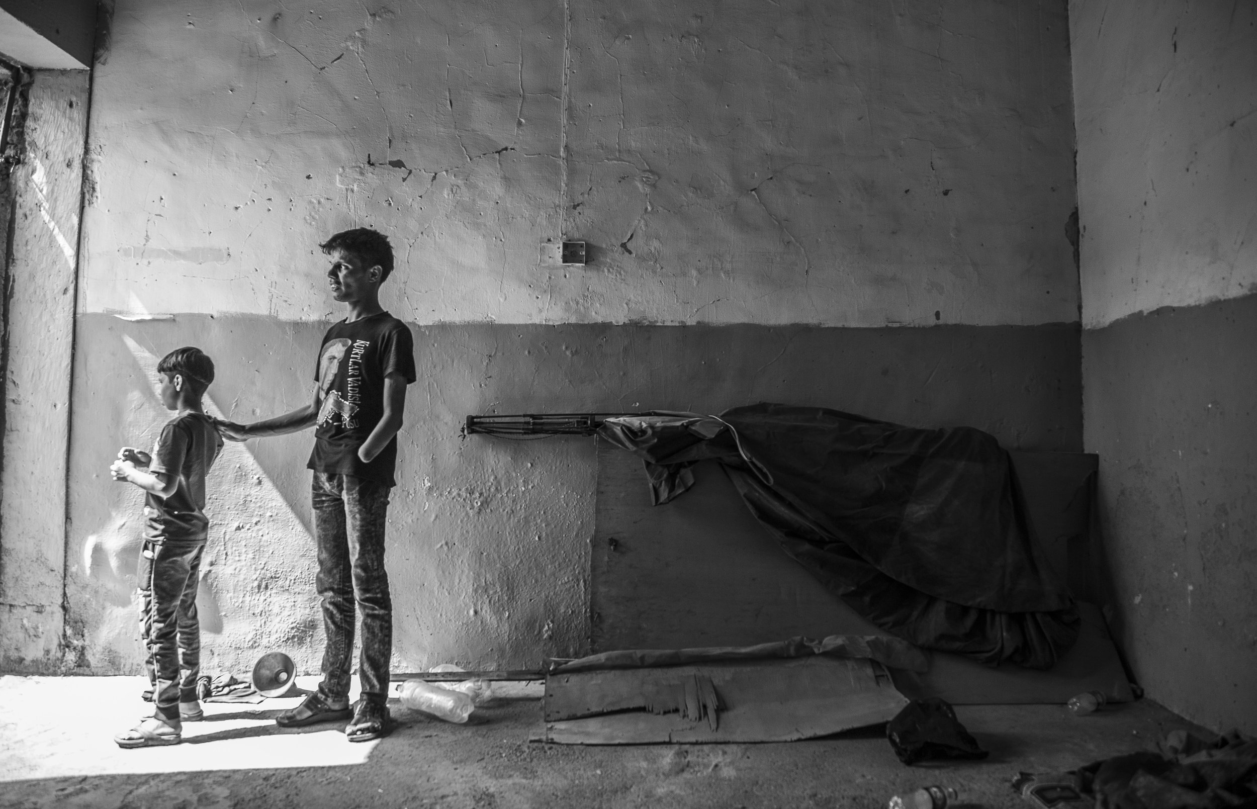 A young man and boy living in a group of children whose families were killed by ISIS.