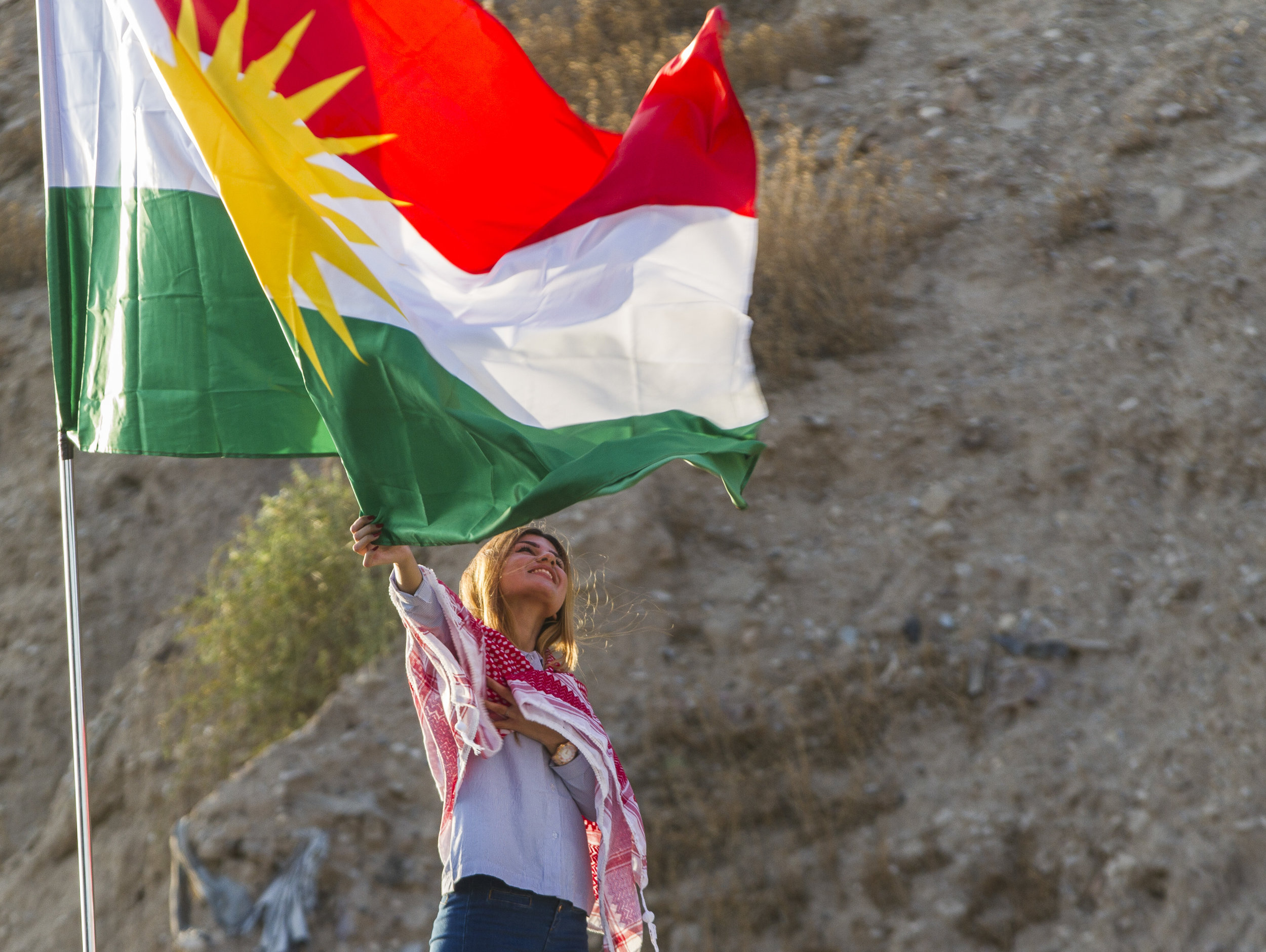 A woman poses next to the Iraqi Kurdistan flag in Eribl.