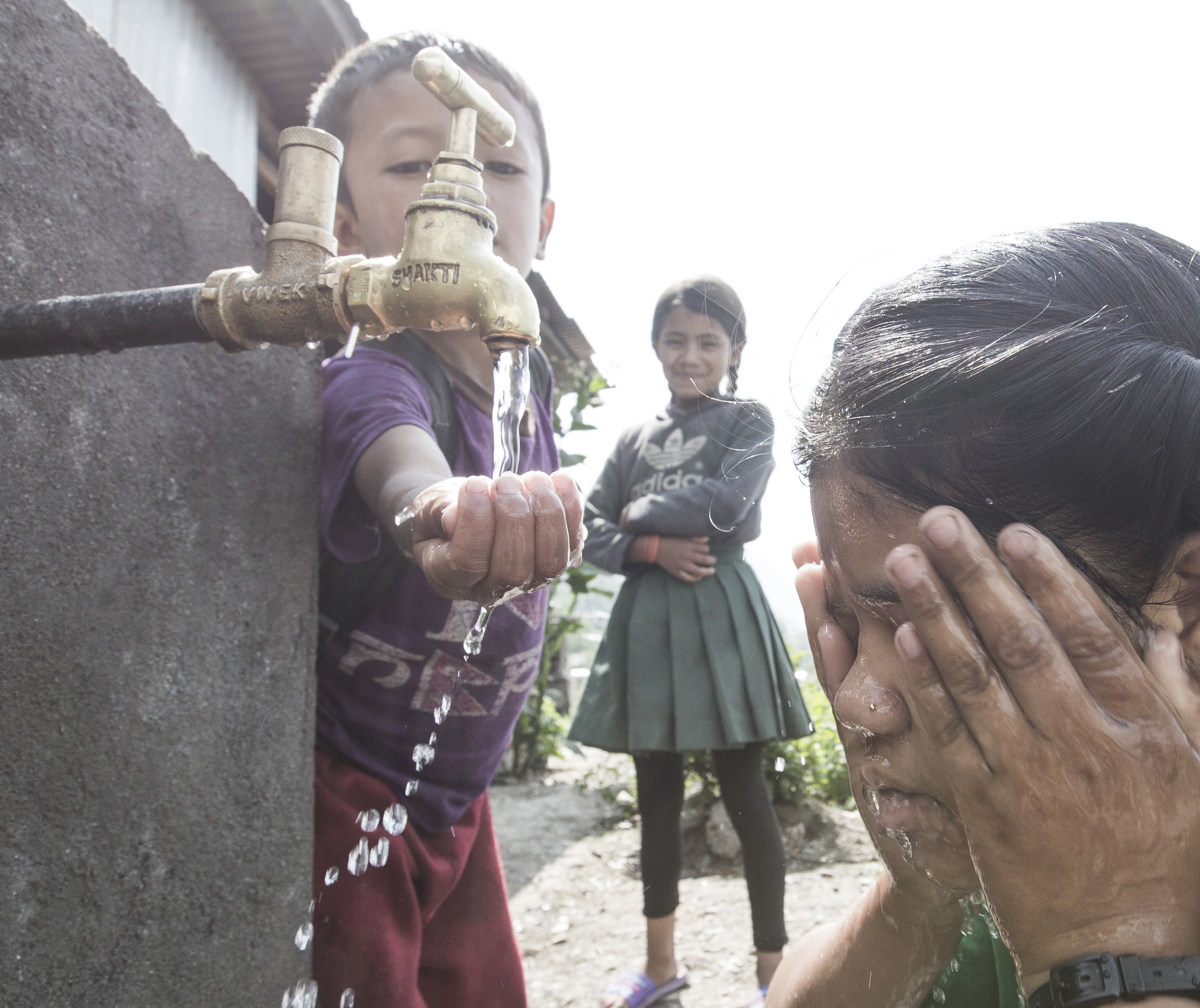Children enjoy fresh water from the tap after the community completed a water infrastructure project.