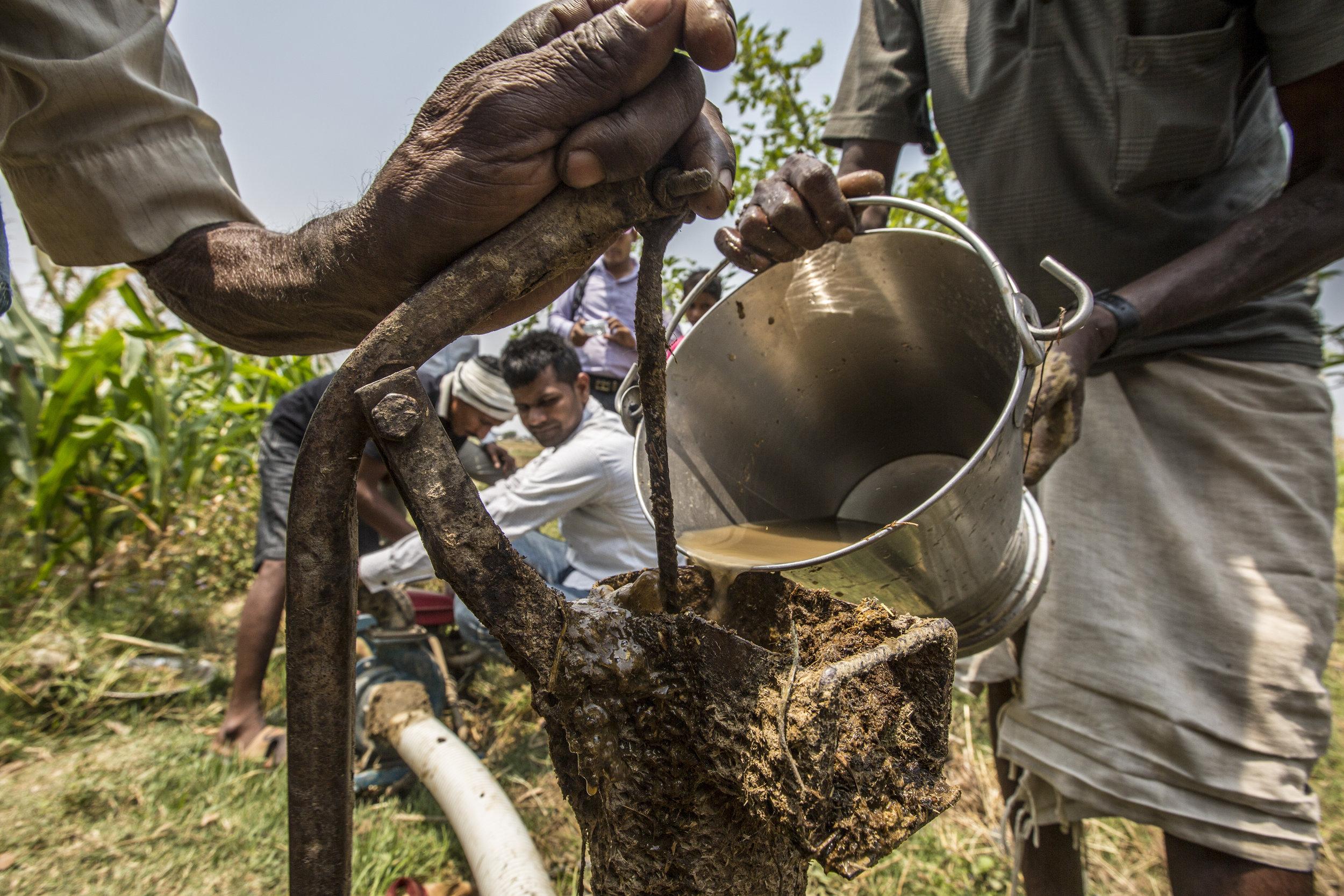 Villagers prime an irrigation pump, part of a Sajhedari infrastructure project.