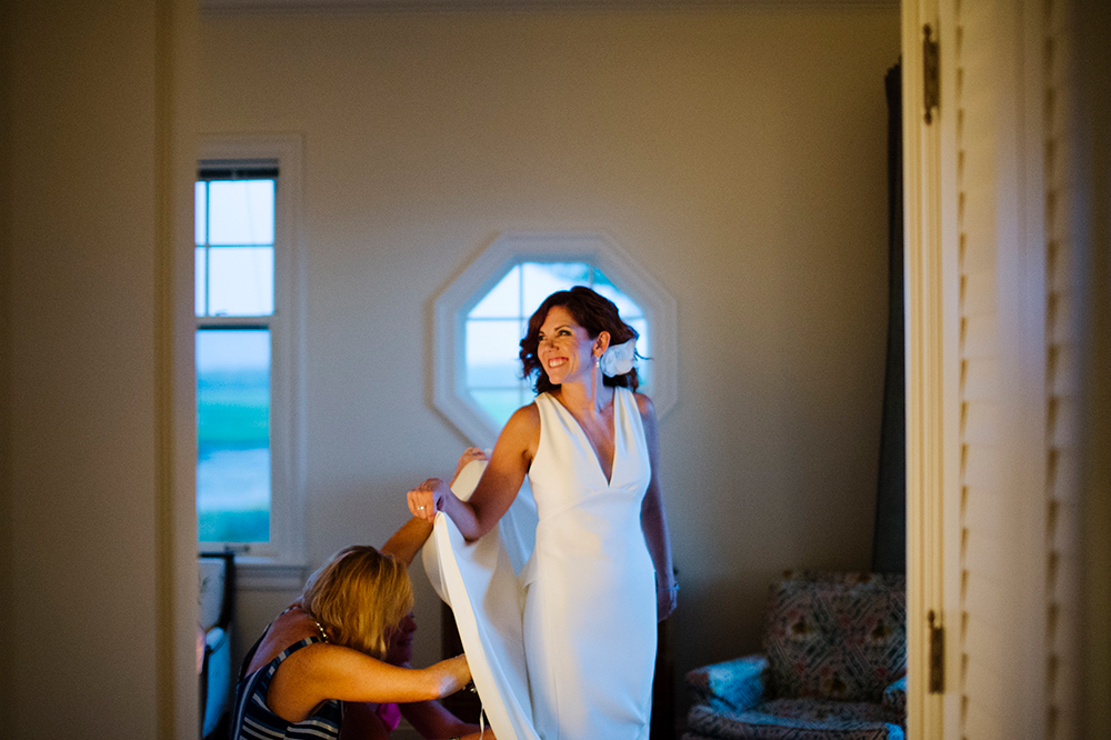 Bride getting her dress bustled after private outdoor ceremony