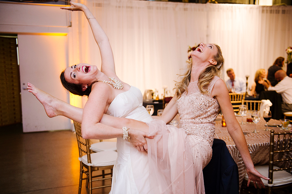 Bride and bridesmaid dance at wedding at the Artists for Humanity, Boston