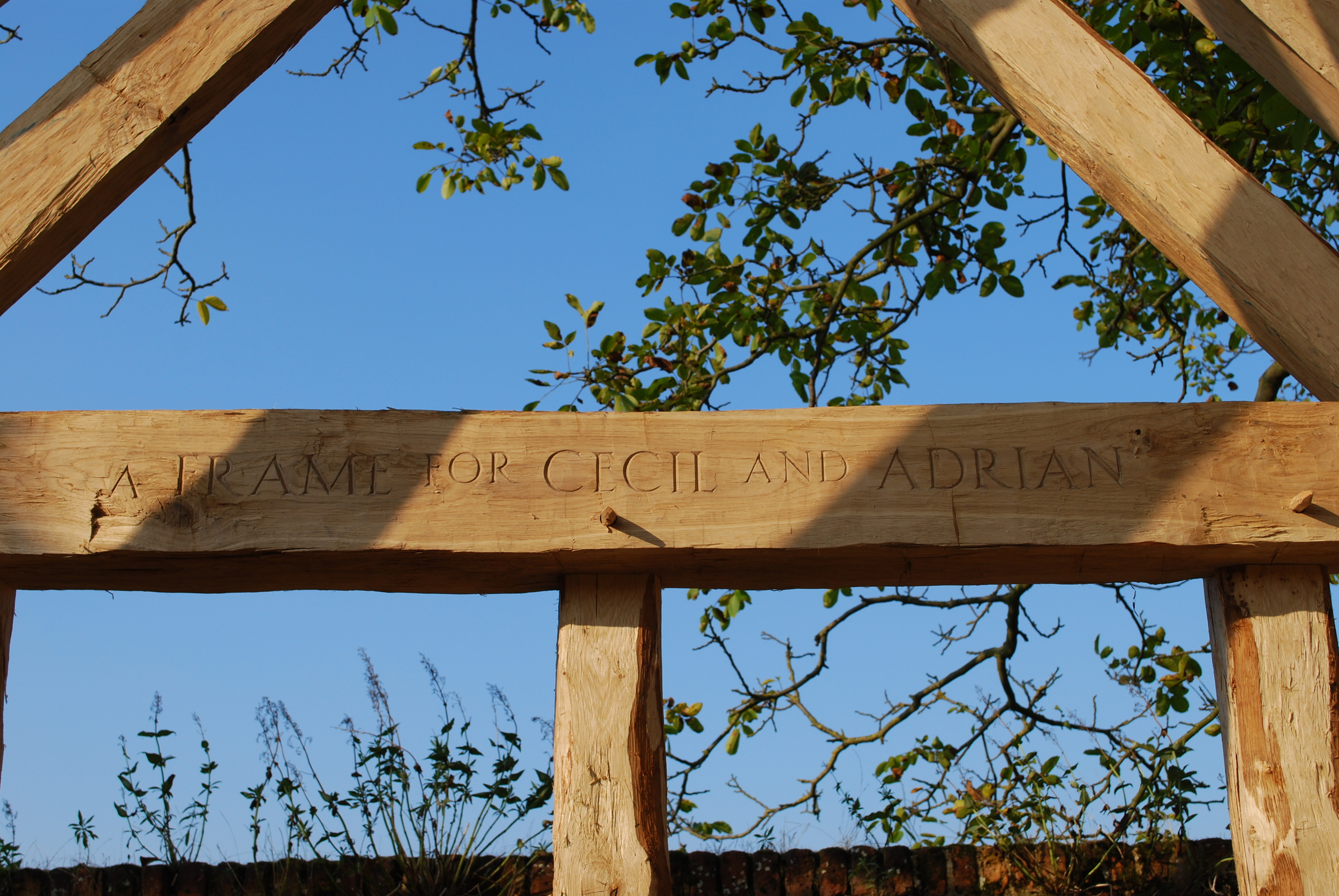 "The inscription on the inner tie beam carved by Rupert Newman says ""A frame for Cecil and Adrian."" Cecil is Cecil Hewett, author of a number of pivotal books on historic carpentry. Adrian is Adrian Gibson, a colleague of Cecil and a great historic buildings specialist. Adrian and Laurie Smith worked on the geometry of the great barns at Cressing Temple."