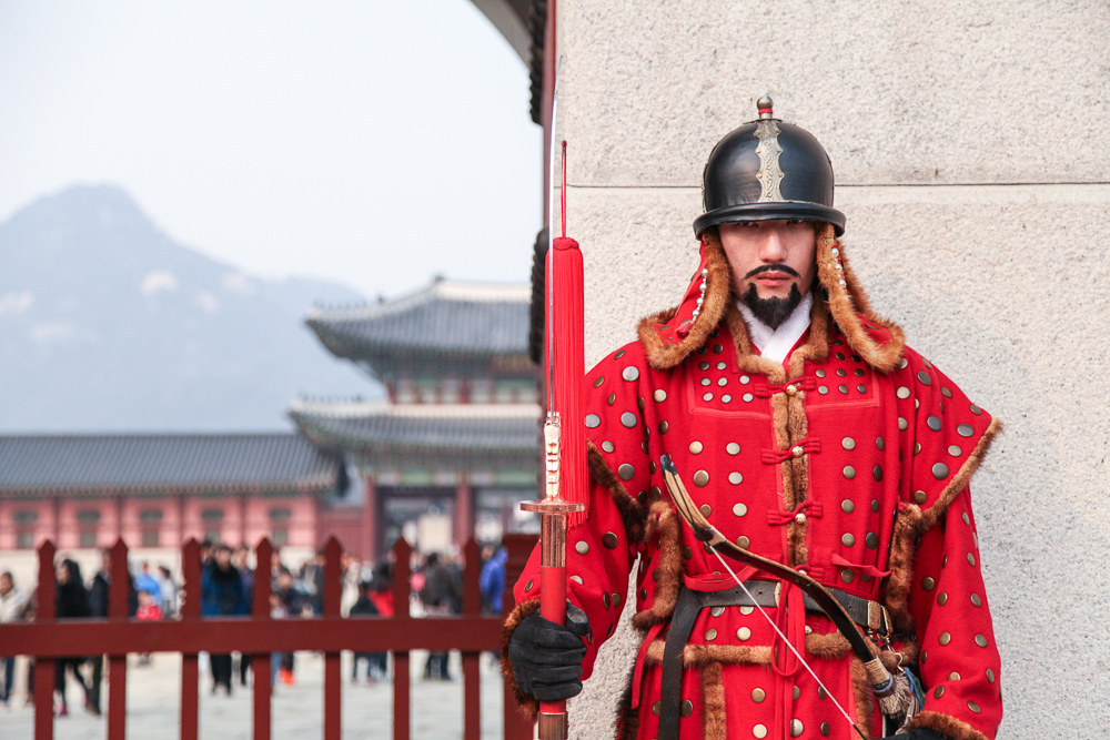 The very happy man acting as a royal guard. Feel free to stare at him all day. Just don't touch him.