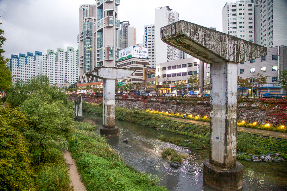 Three pillars left from the Cheonggye Overpass as a reminder of the stream's past.