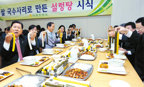 Choi Won-byeong (far left), the chairman of the National Agricultural Cooperative Federation, and guests holding up garaetteok ( JoongangDaily )