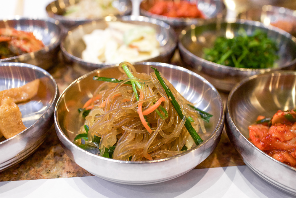 Japchae. Korean glass noodles stir-fried in sesame oil with carrots, green onions, onions, and spinach.