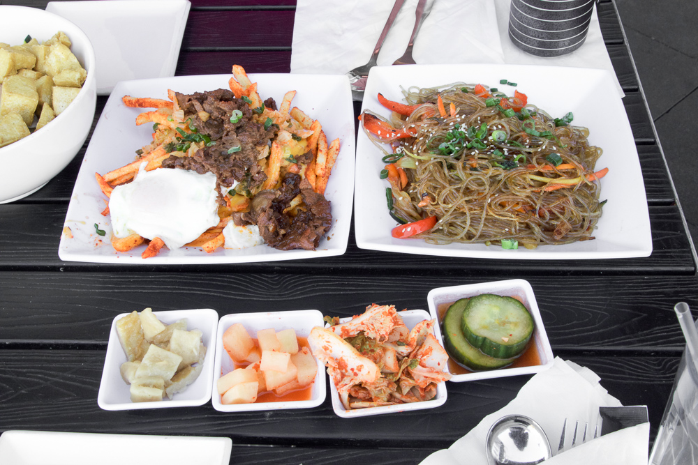 From way left to right: Bibimbap with Fried Tofu, Oppa Gangnam Fries, Japchae. Bottom: Banchan (Korean side dishes).