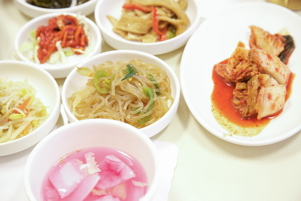 Common banchan of seasoned sprouts, japchae, kimchi, and fishcakes.