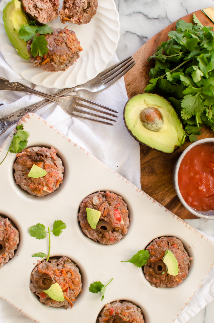 Super simple to throw together and quick to cook, Veggie-Loaded Mini Taco Meatloaves are a fun flavor twist on a classic dinner dish! Loaded with oodles of veggies and squeaky clean ingredients, these miniature meatloaves cook up in half the time of traditional meatloaf and are perfect for weeknight dinners! Paleo, gluten free, dairy-free, and Whole30. #whole30meatloaves #carrotrecipesforkids #hiddenveggierecipesforkids #Paleomeatloaves