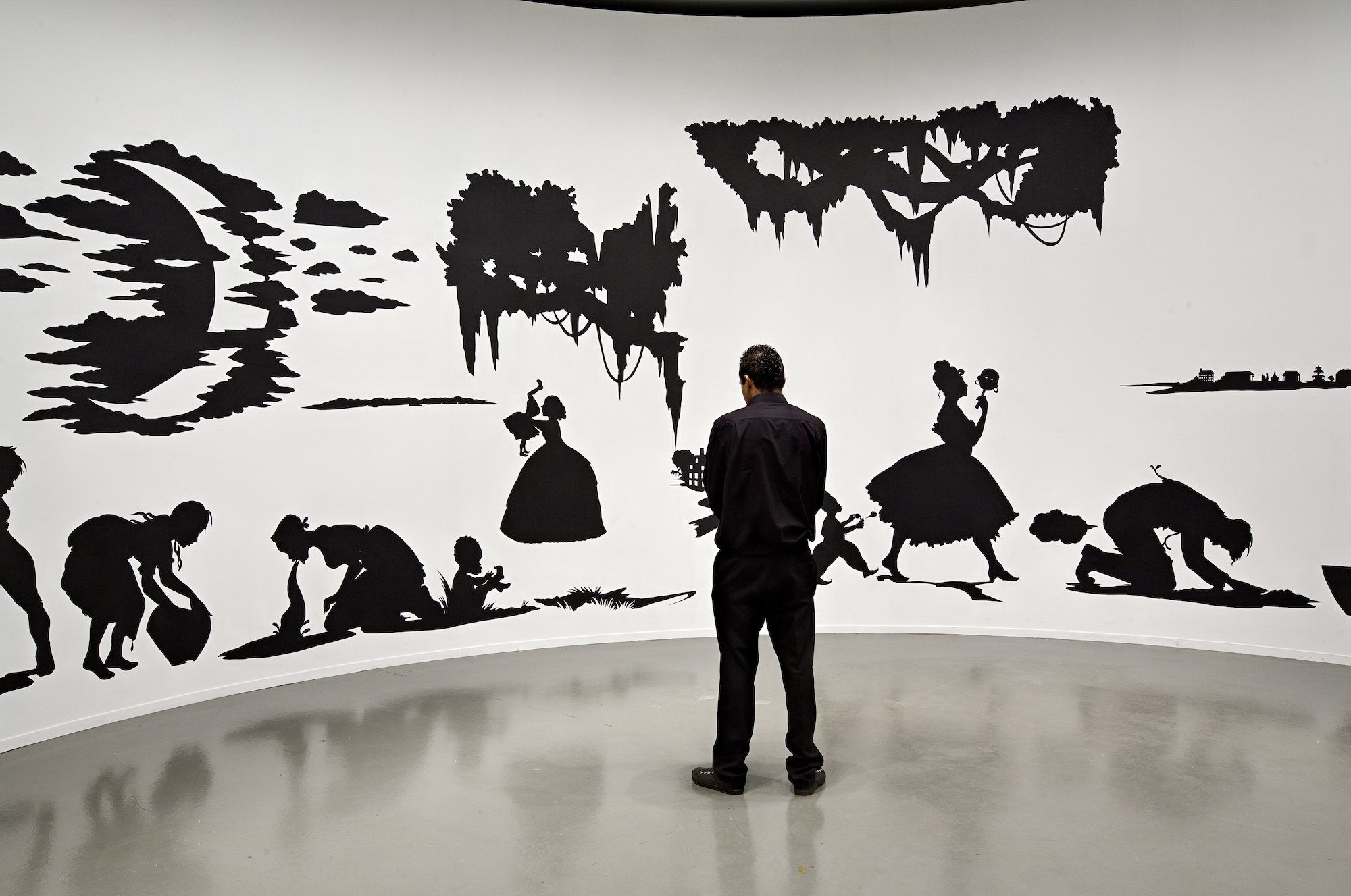 """Kara Walker, Slavery! Slavery! Presenting a GRAND and LIFELIKE Panoramic Journey into Picturesque Southern Slavery or """"Life at 'Ol' Virginny's Hole' (sketches from Plantation Life)"""" See the Peculiar Institution as never before! All cut from black paper by the able hand of Kara Elizabeth Walker, an Emancipated Negress and leader in her Cause , 1997. Cut paper on wall, approx. 144 x 1,020 inches.ARC/Musée d'Art moderne de la Ville de Paris, 2007. Photo: Florian Kleinefenn"""