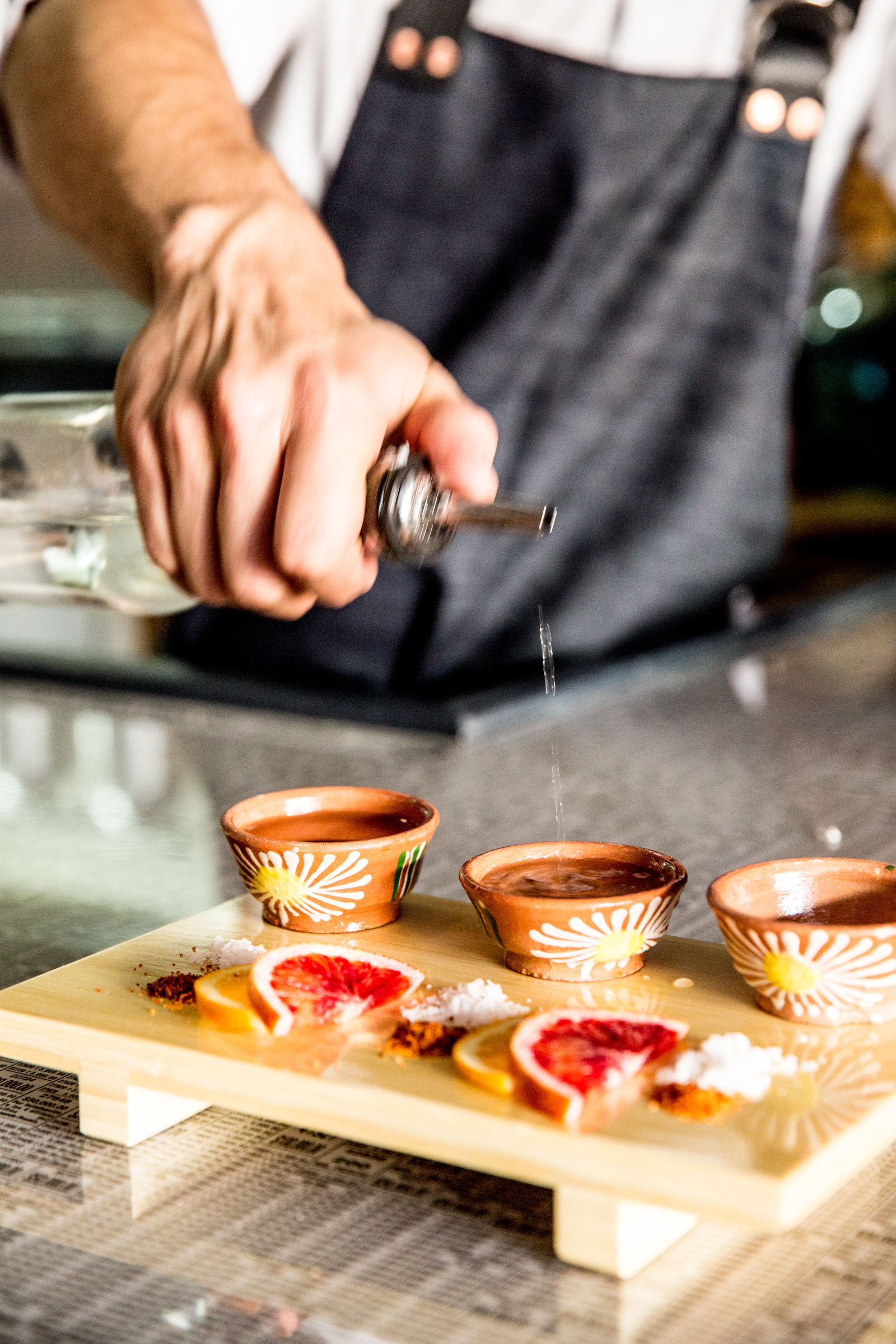 Bartender pouring shots of mezcal in traditional cups with citrus slices, salt, and chili salt