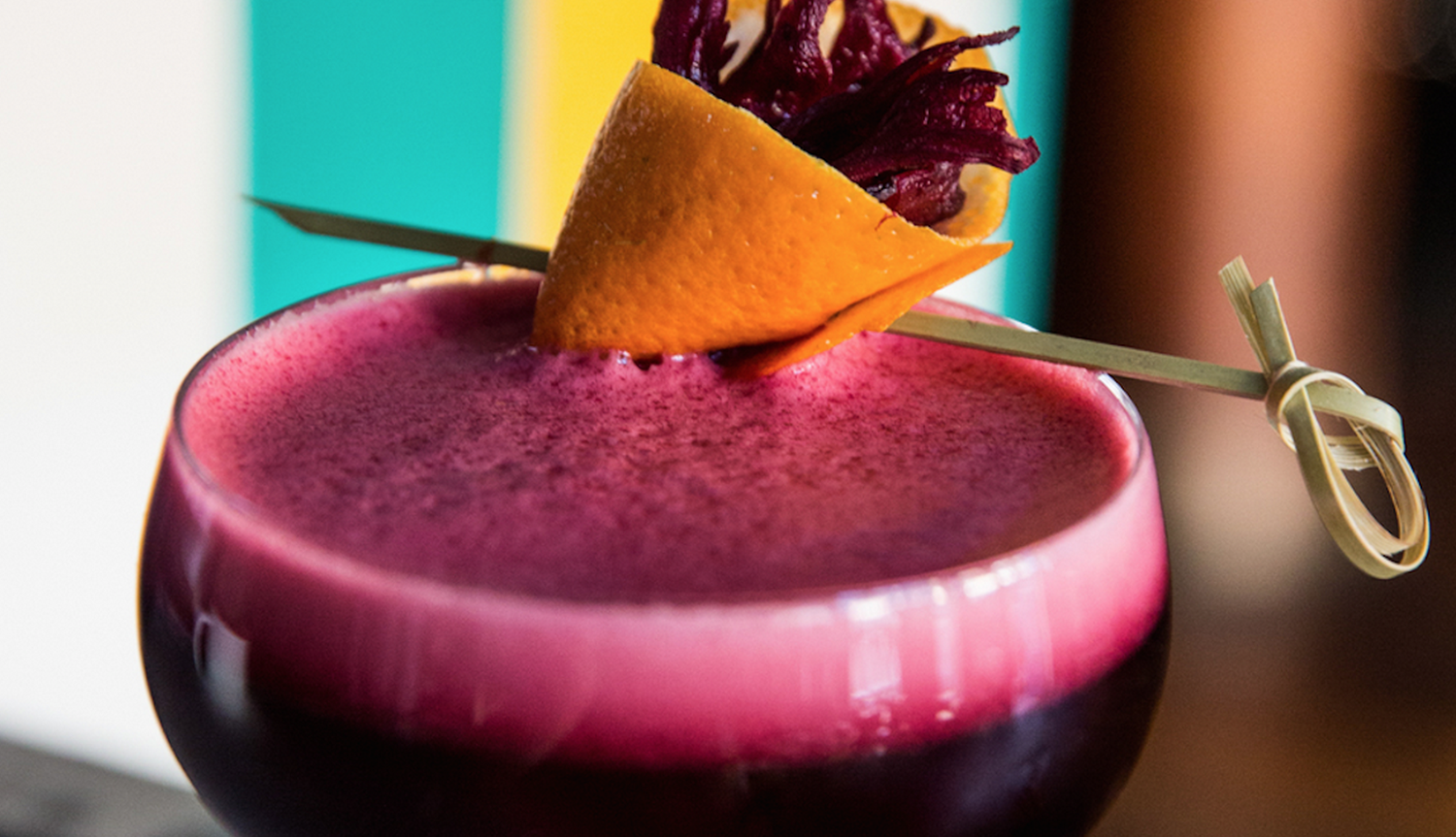 Close up of bright red-violet colored cocktail with an orange twist