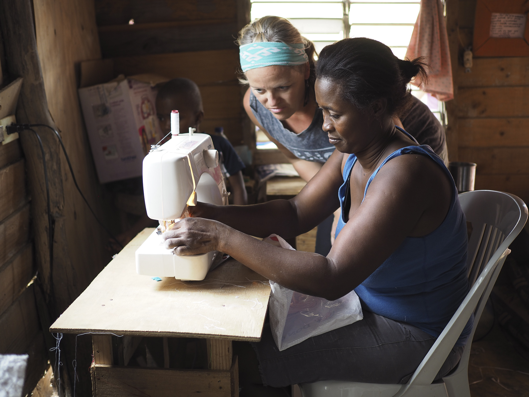 Kelly and Gracia working in the small shack that the women have rented with their own money to store their sewing machines and jewelry making supplies.