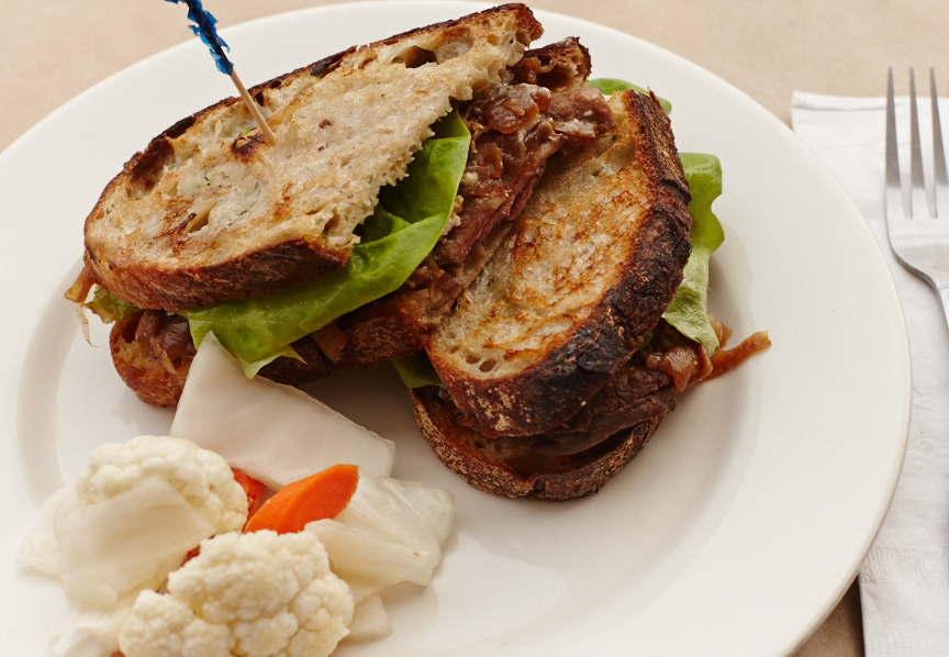 Steak sandwich with blue cheese-butter, caramelized onions, and bibb lettuce on Banshee Tuscan white
